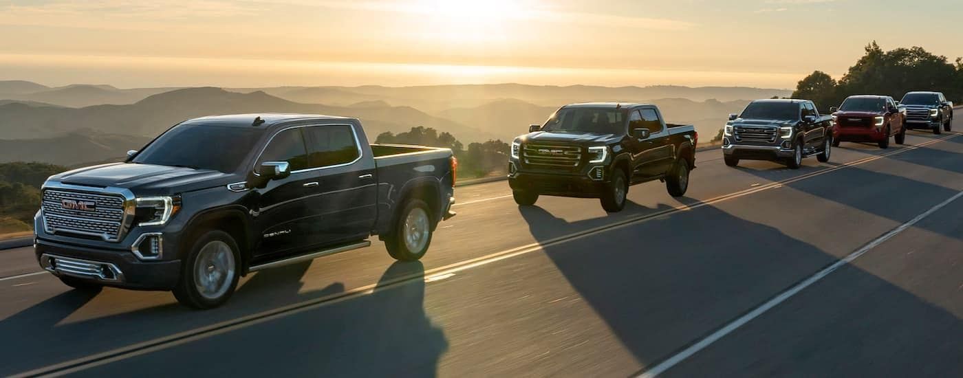 A line of 2020 GMC Sierra 1500s, popular among GMC trucks, are driving with mountains and a sunset in the distance.
