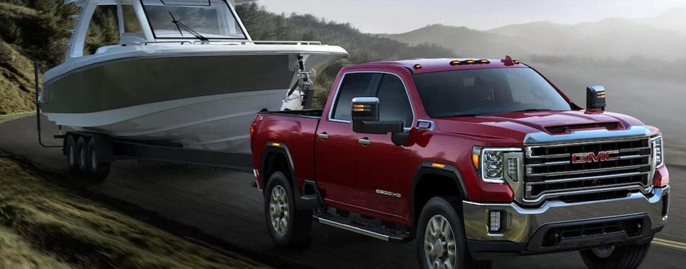 A red 2020 GMC Sierra 2500HD is towing a large boat next to a foggy lake.
