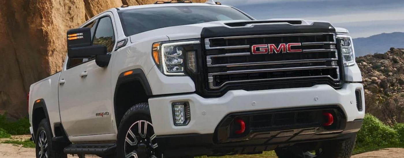 A white 2020 GMC Sierra AT4 is parked on a dirt hill with a large mountain in the distance.