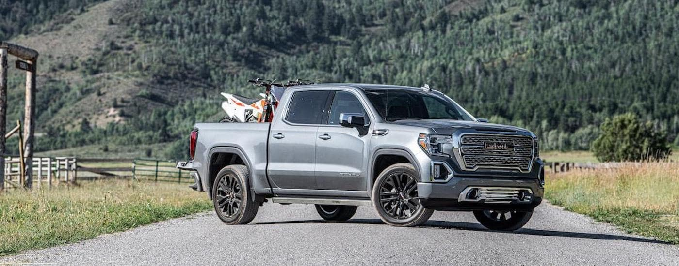 A silver 2020 GMC Sierra 1500 is parked on a dirt road next to a farm with mountains in the distance.