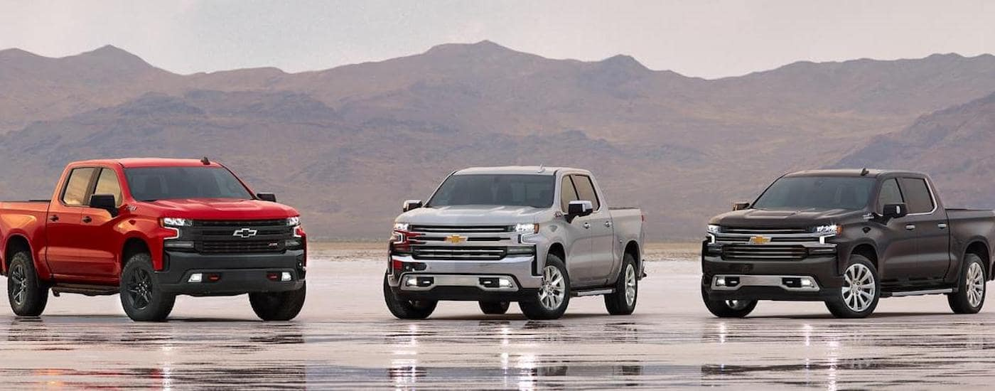 A red, silver and black 2020 Chevy Silverado's on a salt flat with mountains in back outside of Corsicana, TX.