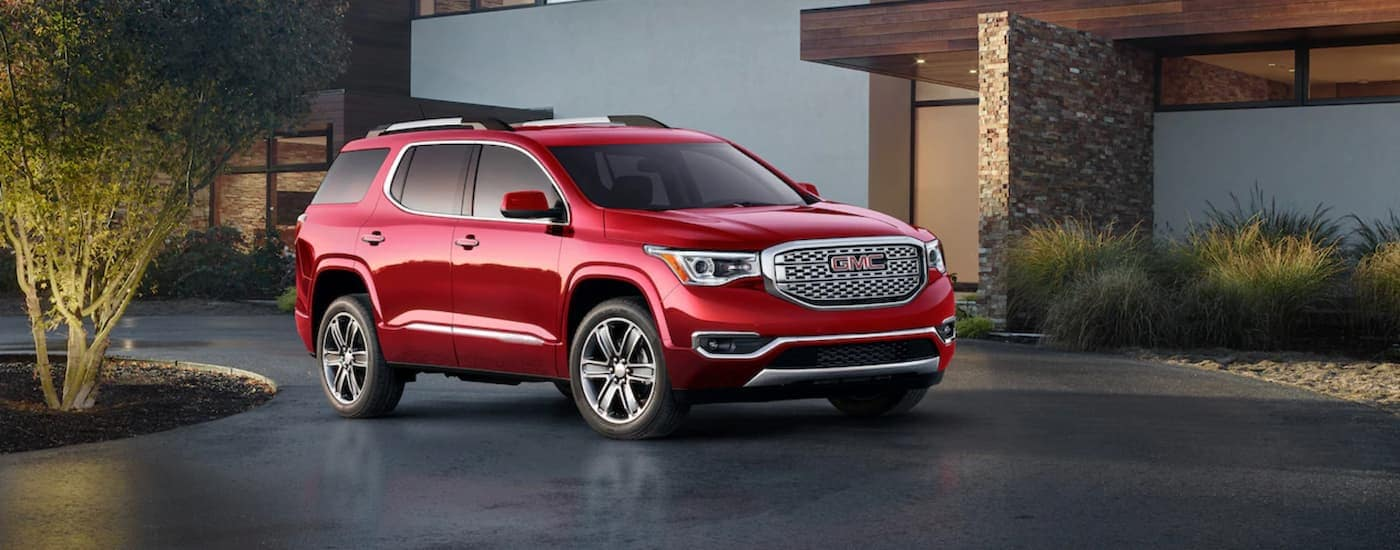 A red 2019 GMC Acadia is parked in front of a modern house after leaving Texas GMC dealers in Corsicana.
