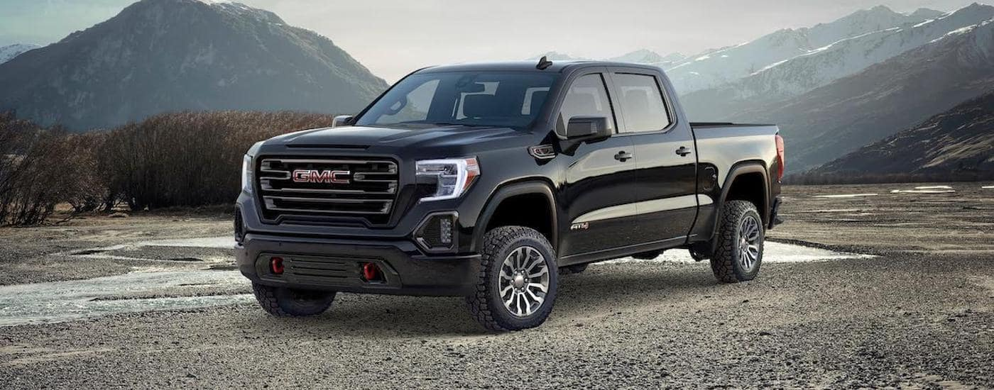 A black 2020 GMC Sierra AT4 is parked in a dirt field with mountains in the distance.