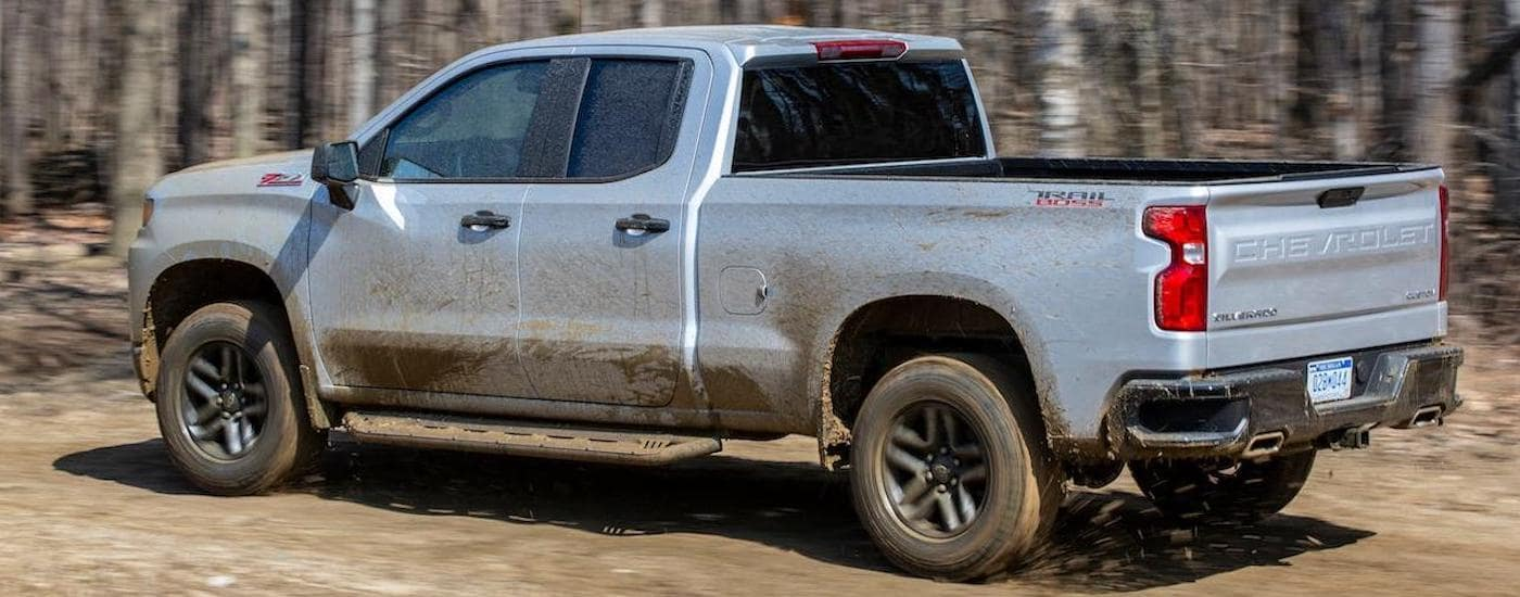A silver 2020 Chevy Silverado TrailBoss is driving on a dirt track near Corsicana, TX, and covered in mud.