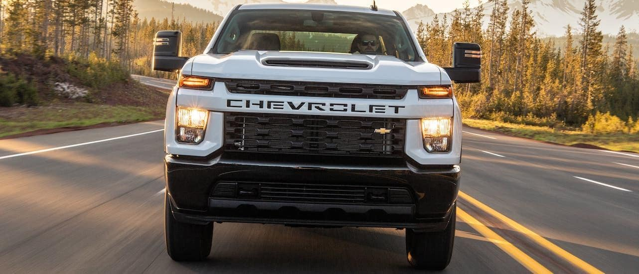 A white 2020 Chevy SilveradoHD is shown from the front driving on a mountainous highway.