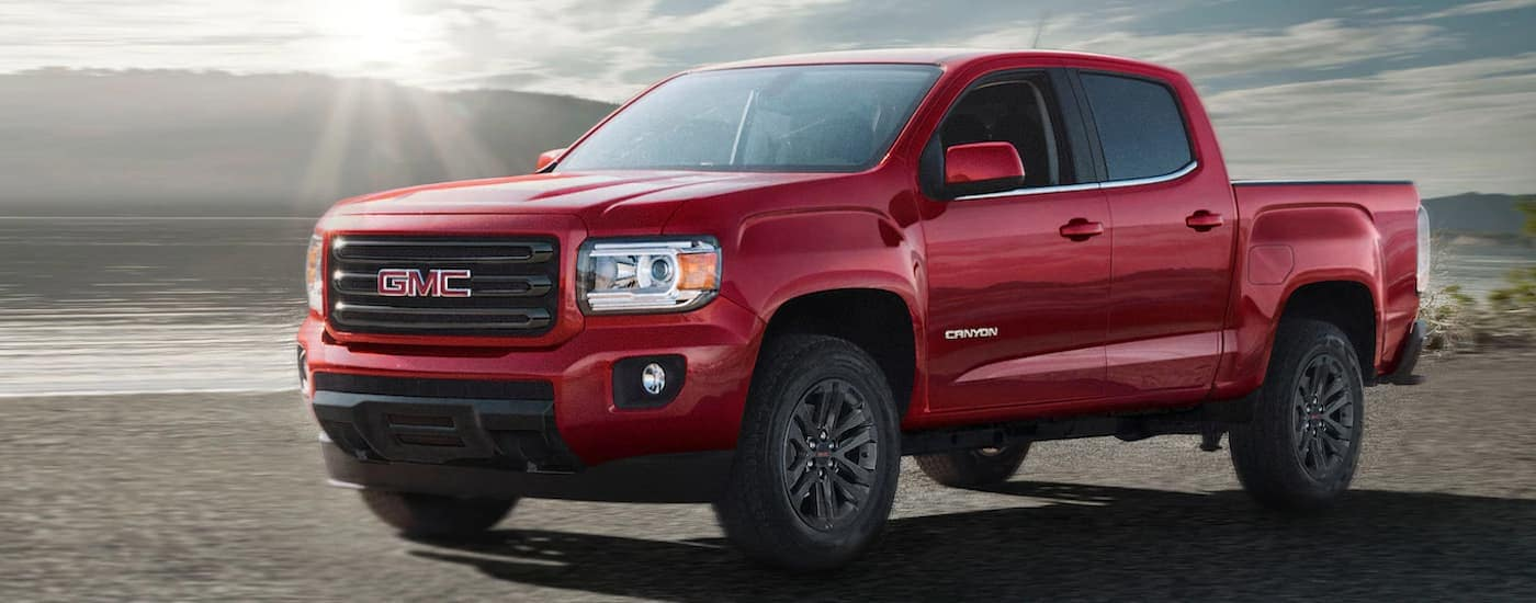 A red 2019 GMC Canyon is parked in front of water with a low sun and is one of the popular trucks for sale in Dallas, TX.