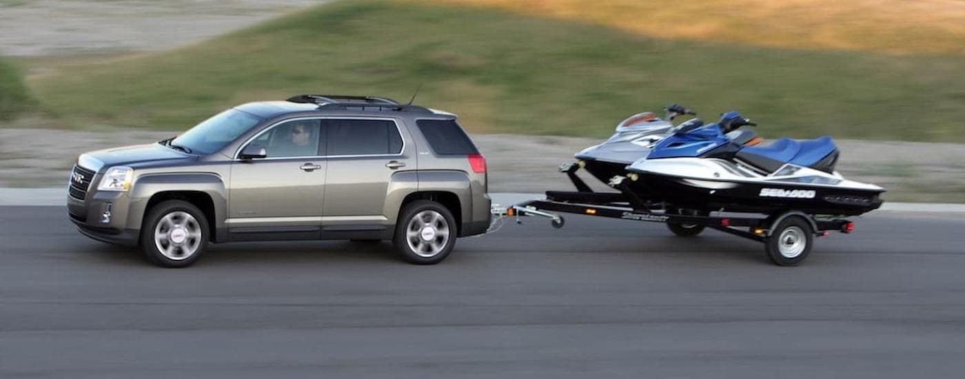 A grey 2015 GMC Terrain is pulling jet skis on a trailer.