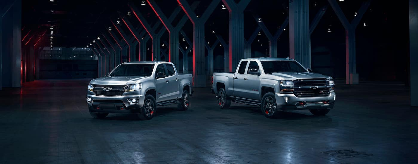 Two 2018 Chevy trucks, a silver Colorado and silver Silverado 1500 which are popular used Chevy trucks in Waco, TX, are parked in a dark lit garage.