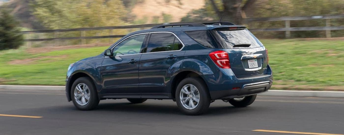 A blue 2016 Chevy Equinox is driving in front of fencing near Corsicana, TX.