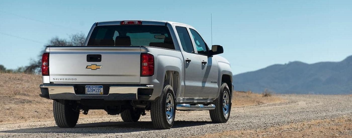 A white 2017 Chevy Silverado is driving on a dirt road towards mountains. The Silverado is one of the popular used trucks for sale in Corsicana, TX.