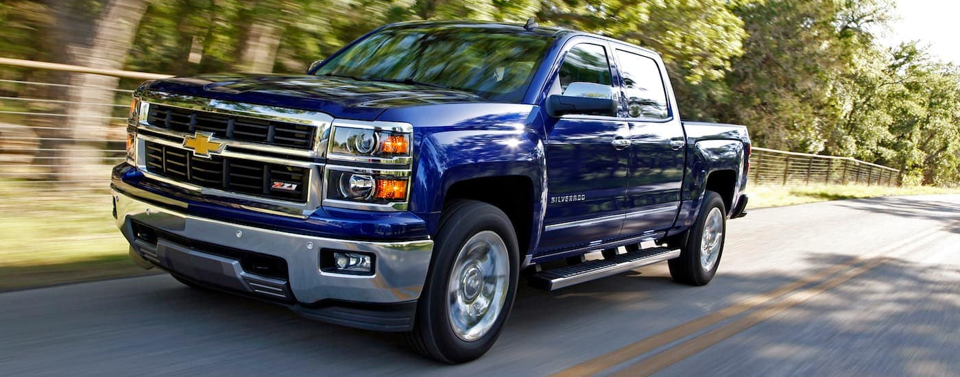 A blue 2014 Chevy Silverado, popular among used Chevy trucks, is driving past a sunny fence.