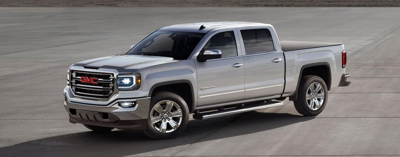 A silver 2017 GMC Sierra is parked in an open cement area and is one of the popular used trucks for sale in Corsicana, TX.