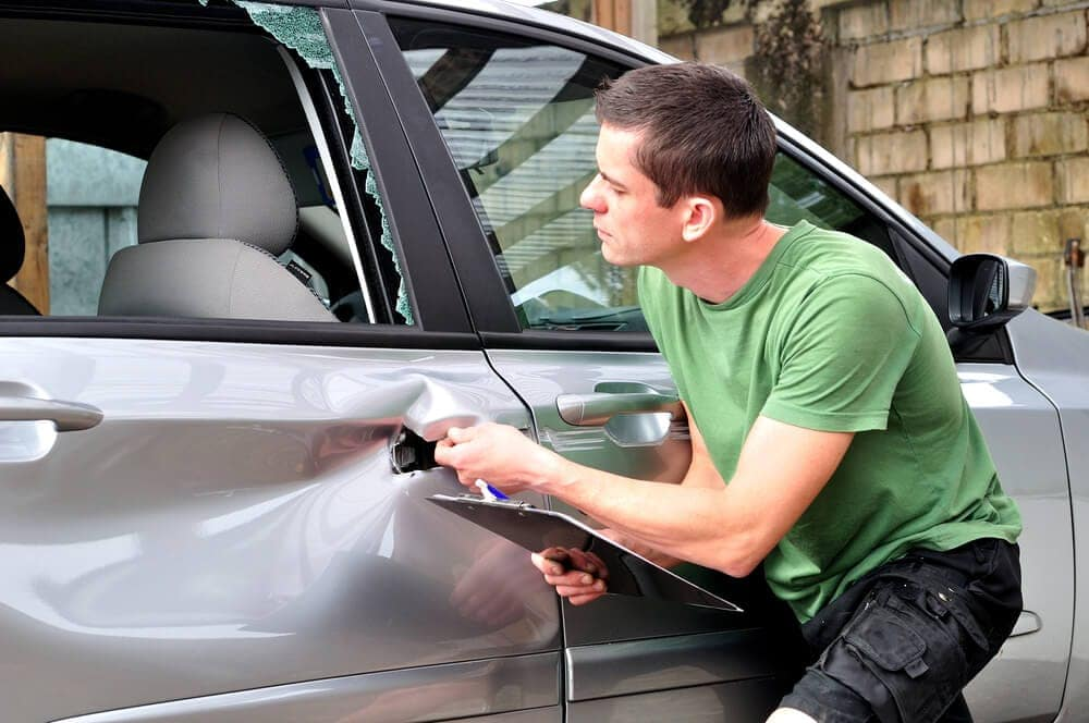 Mechanic checking the damage on a car