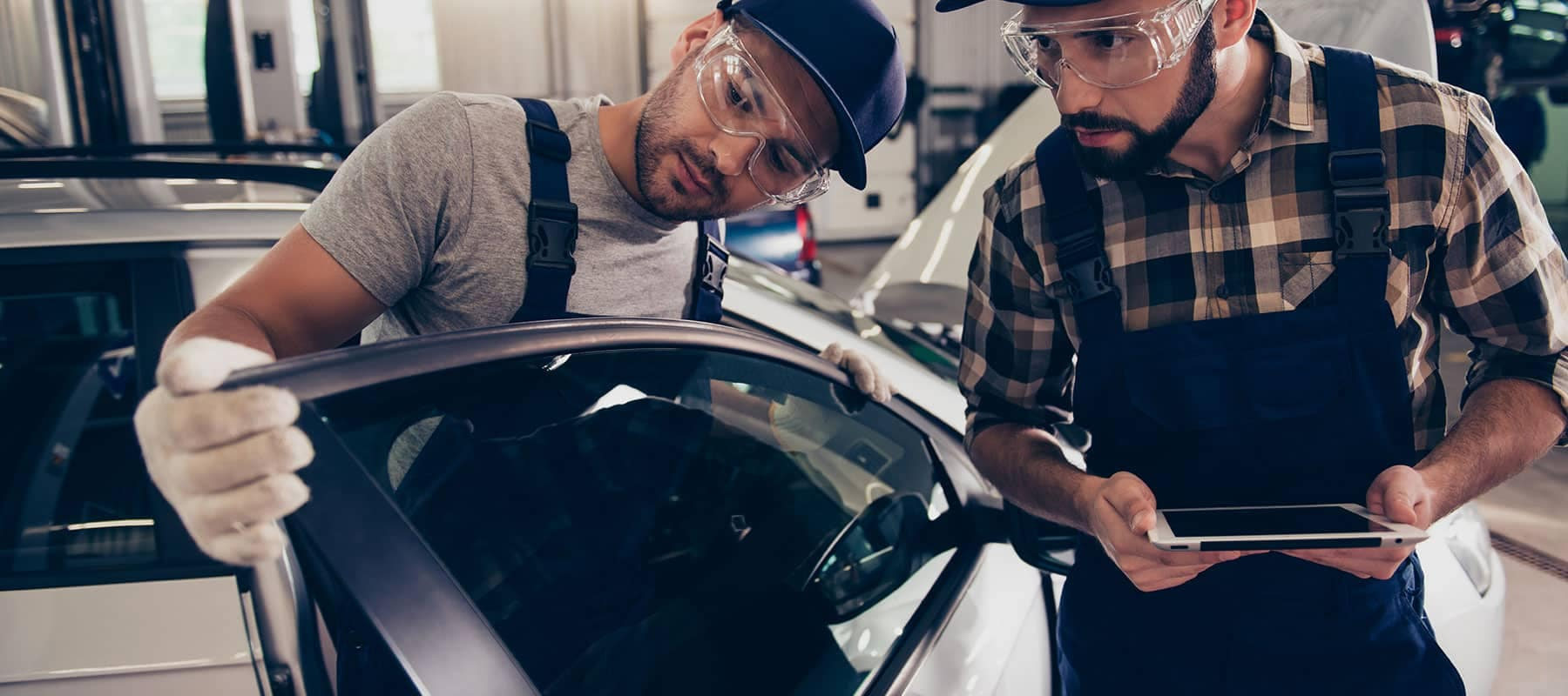 two service technicians examining car door