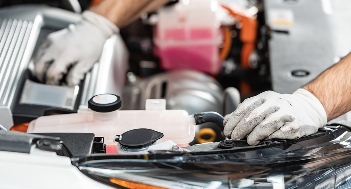 technician adds fluids to car engines