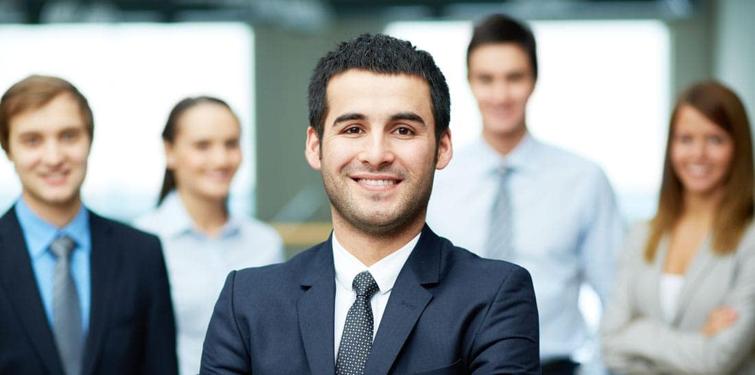 smiling car salesman standing with other salespeople in showroom