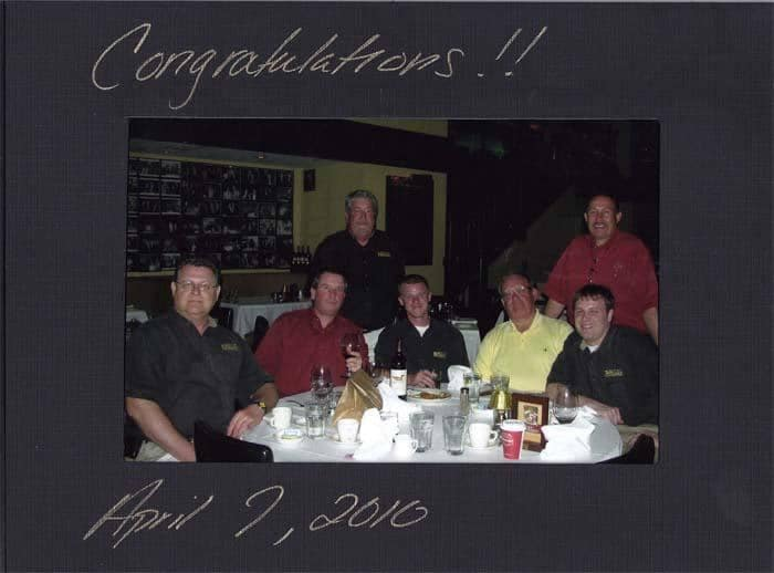 Congratulations photo with dealer employees seated around restaurant table