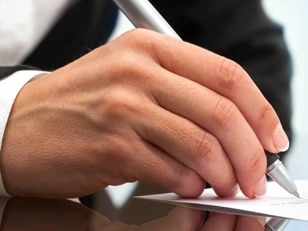 a man's hand signing paperwork on glass table