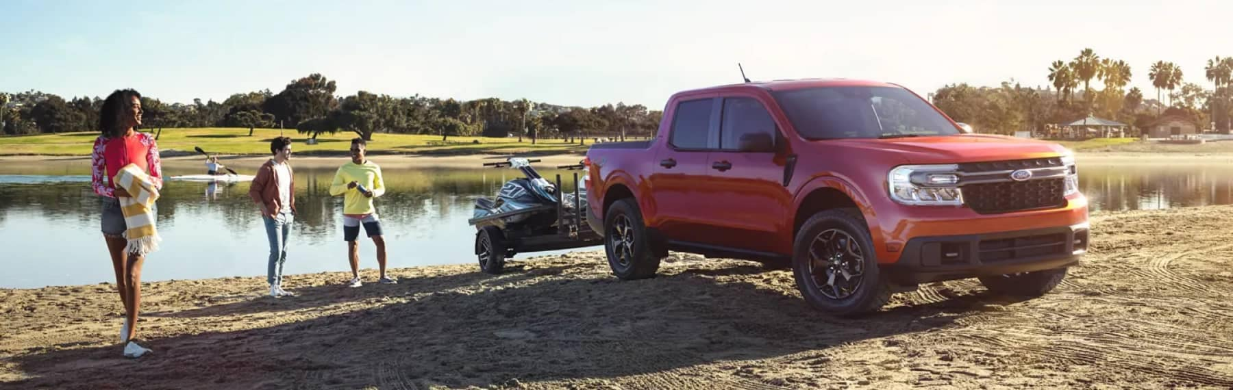 People hanging out by a lake and a parked Ford truck with wave jammer attached