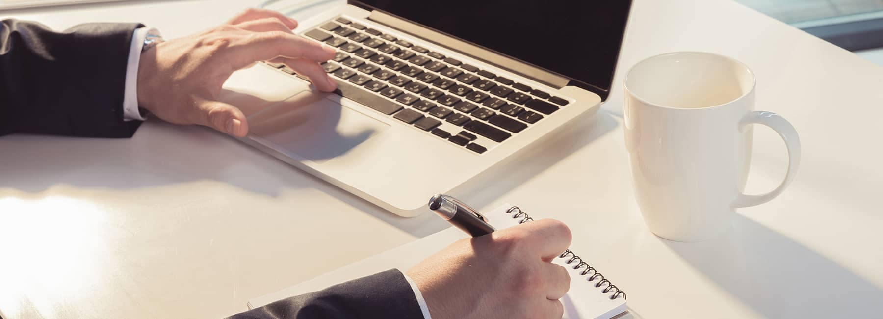 Hand on computer and notepad