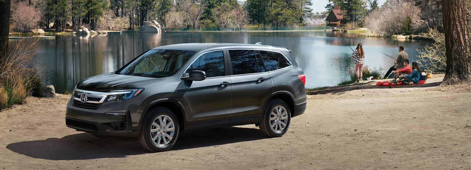 2021 Dark Grey Honda Pilot parked next to a forest lake