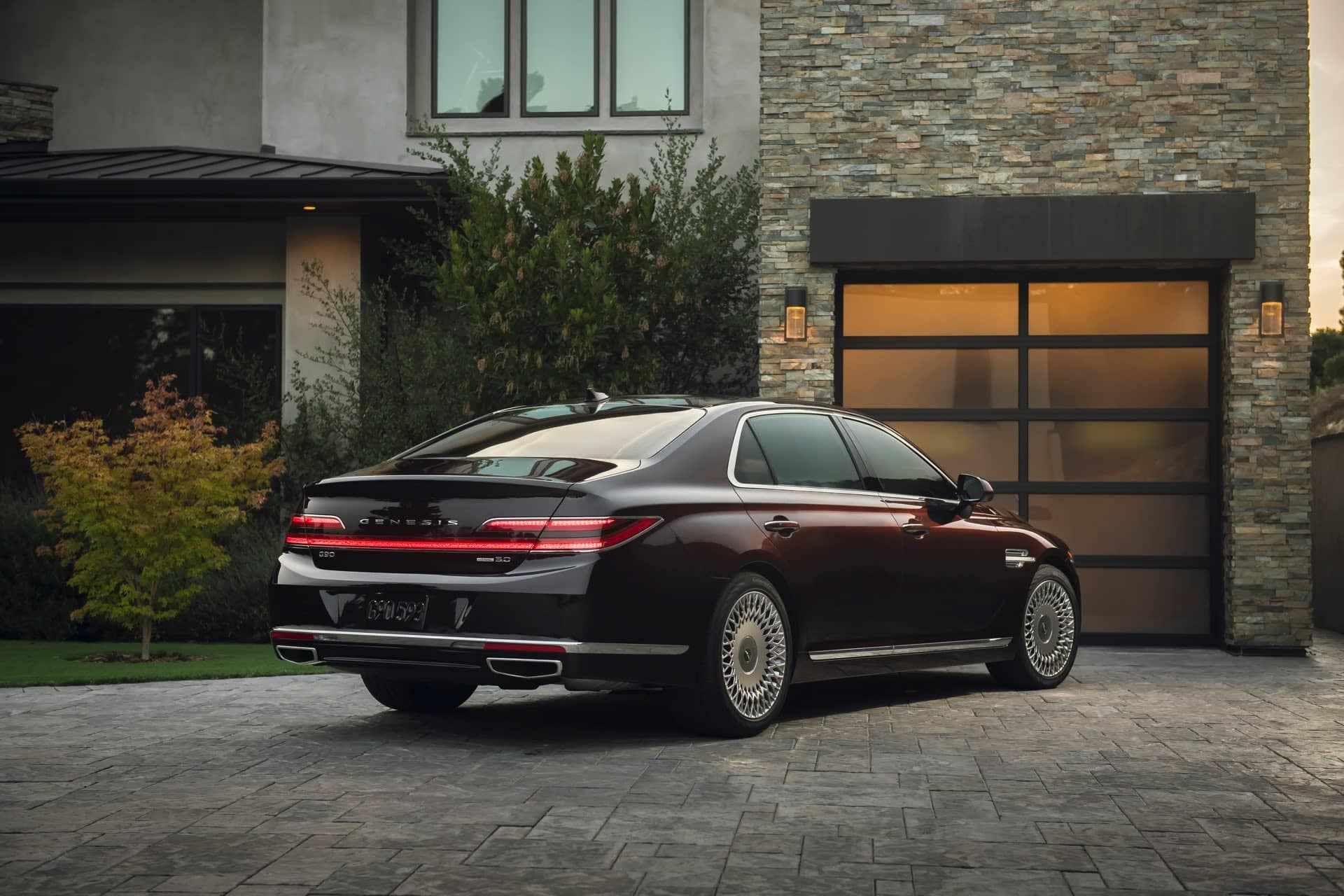 Genesis G90 parked on bricked driveway in front of modern home