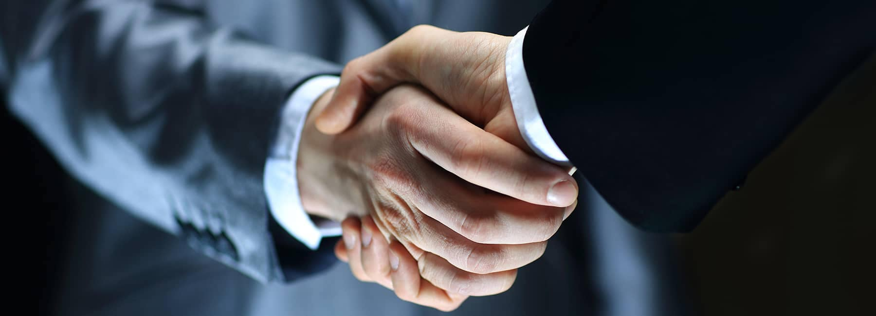 two men in suits shake hands