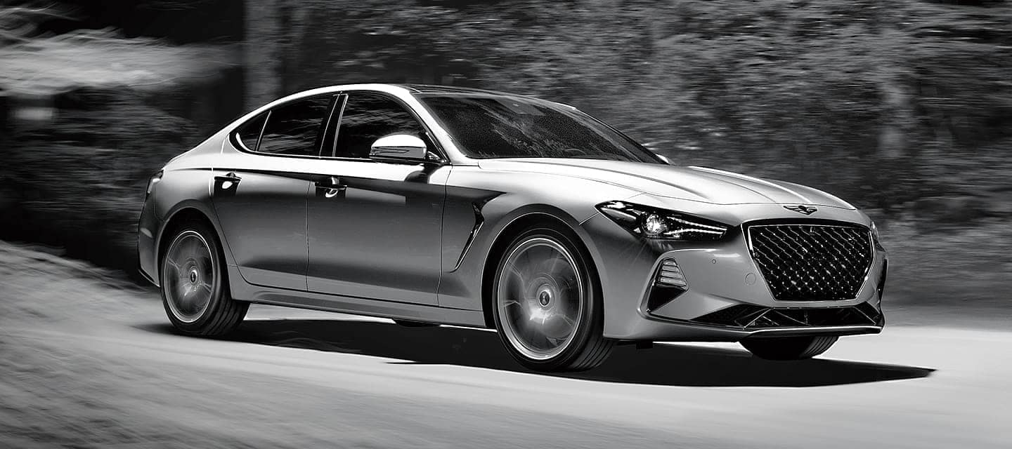silver G70 drives fast on road at night