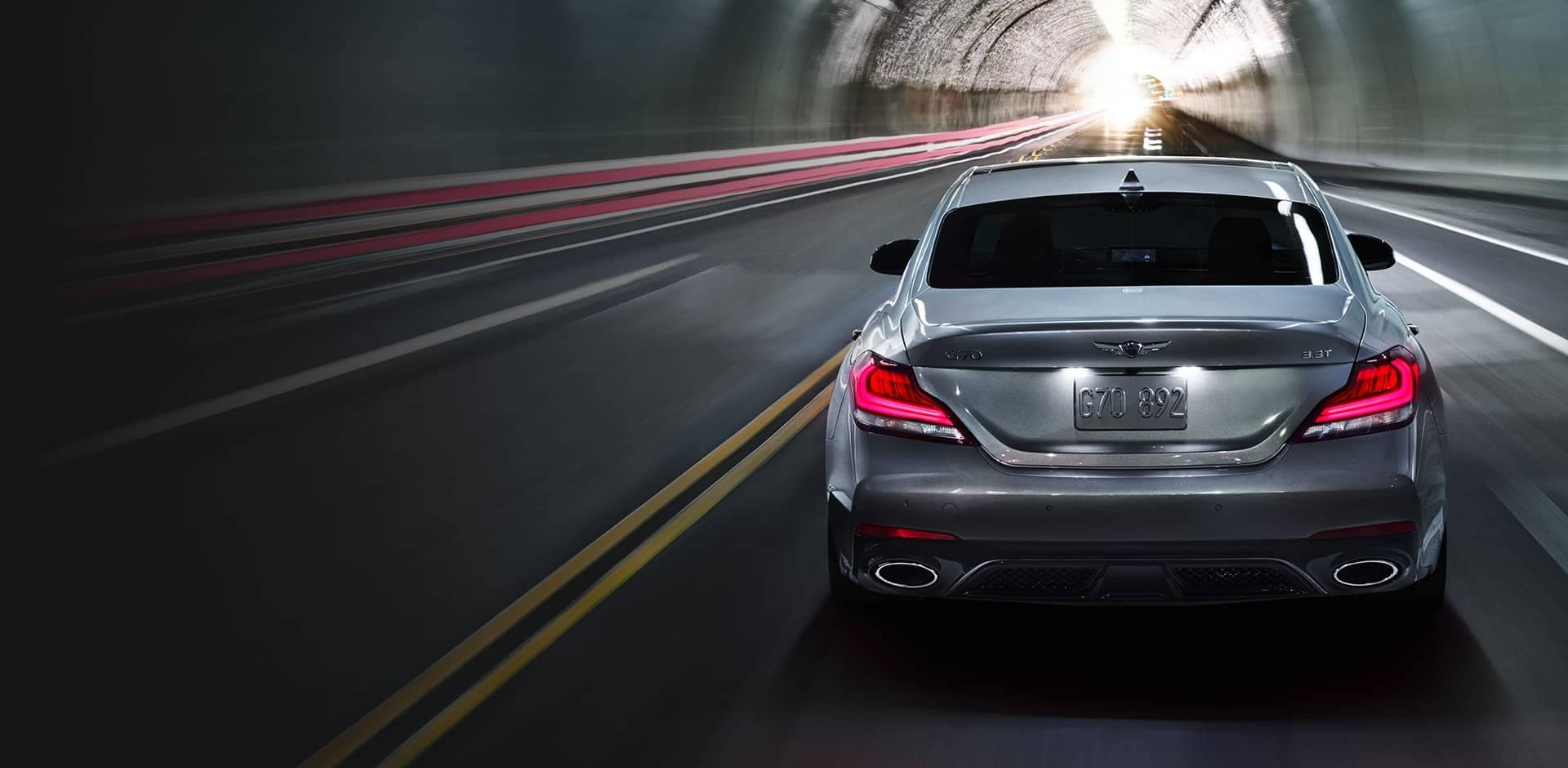 silver G70 driving through highway tunnel