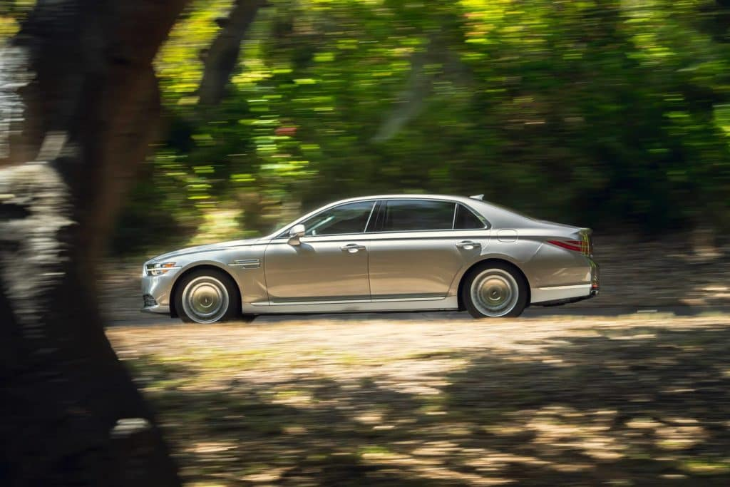 G90 driving down the road in wooded area