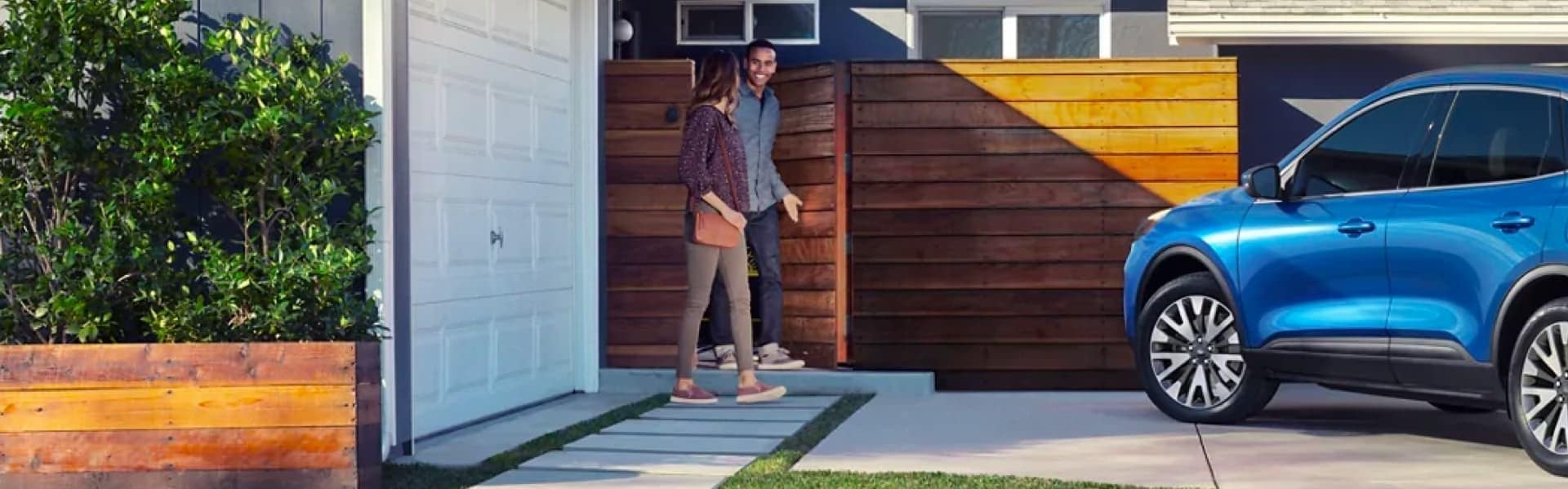 Man and woman walking from the entrance of a house to a blue Crossover SUV
