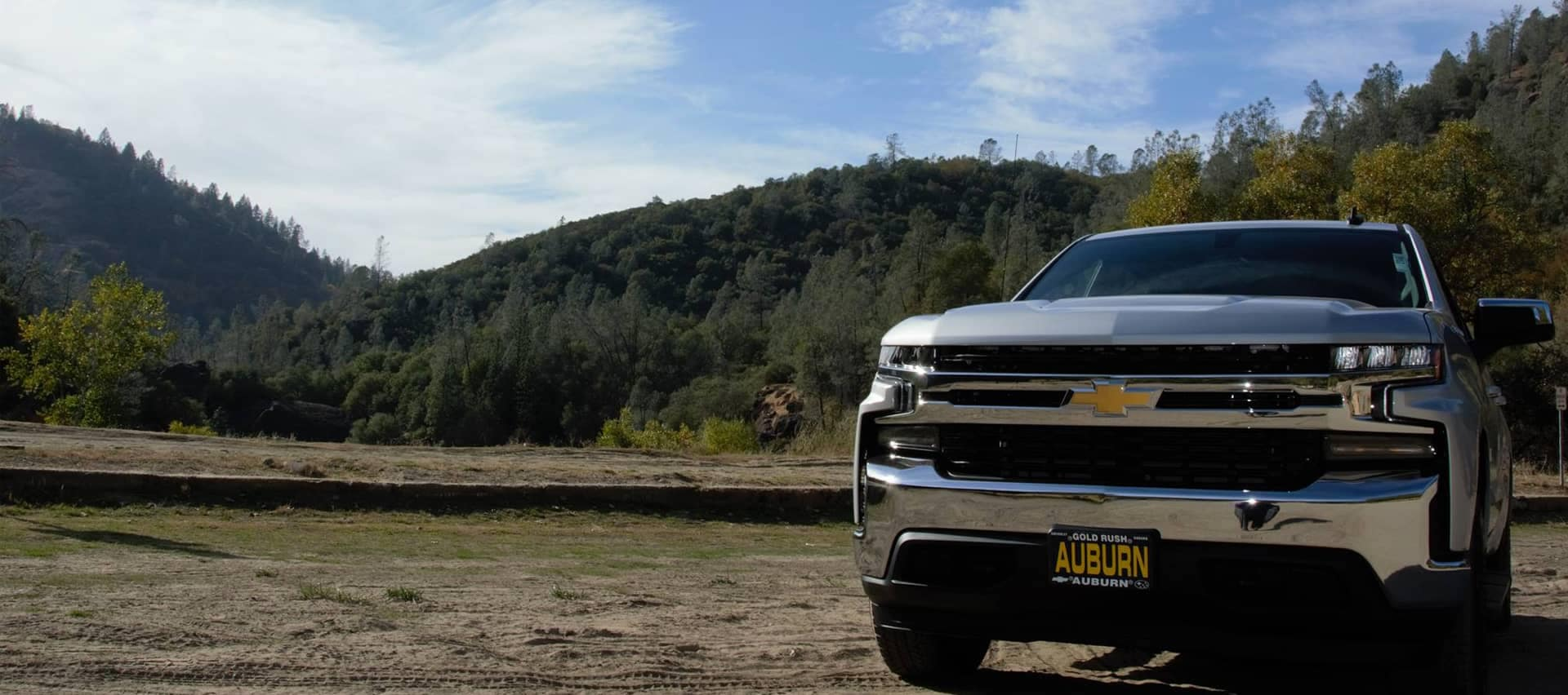 Chevy truck with Auburn license parked in dirt with wooded hills in background