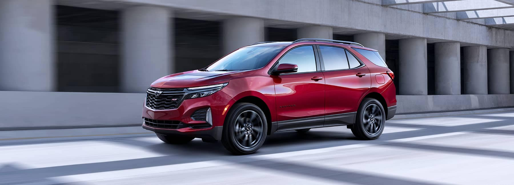 Red 2021 Chevrolet Equinox cruising in the concrete jungle