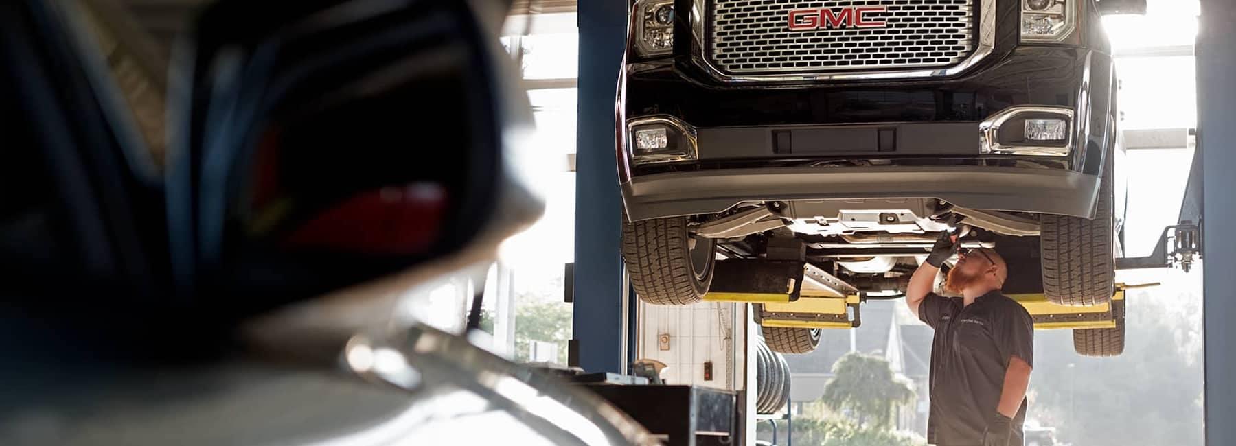 GMC Service Technician looking at underside of GMC vehicle