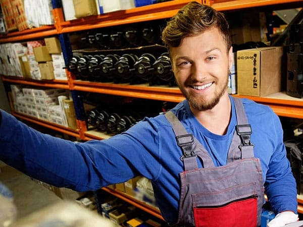 Parts employee with racks full of stock behind him