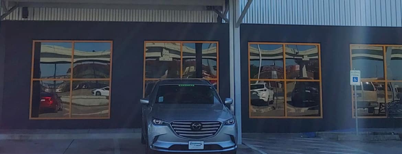 Mazda parked in front of dealer entrance