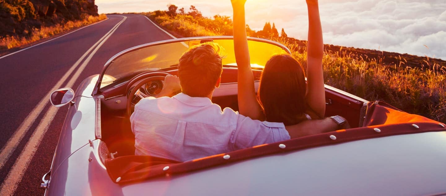 Couple having fun driving on a high-altitude mountain road at sunset