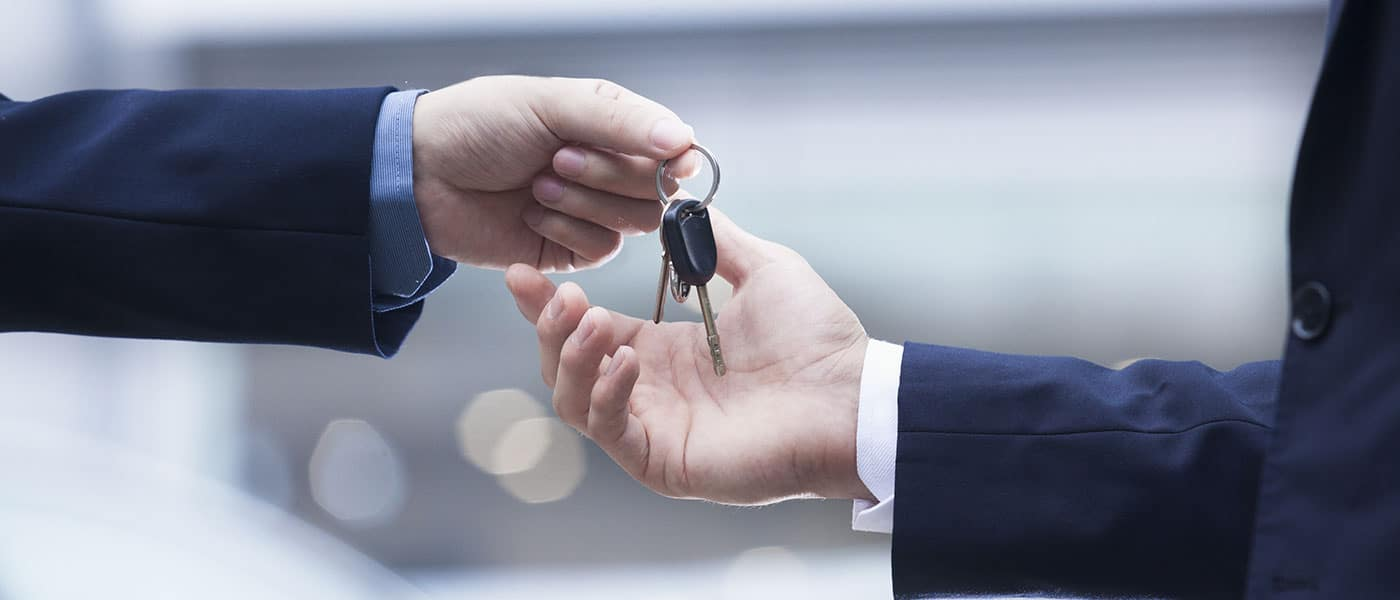person handing car keys to another person