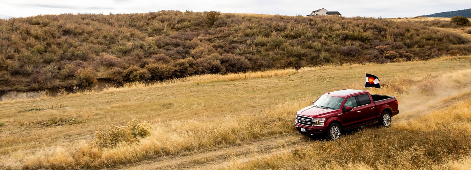 Ford truck driving through a field with the Colorado State Flag