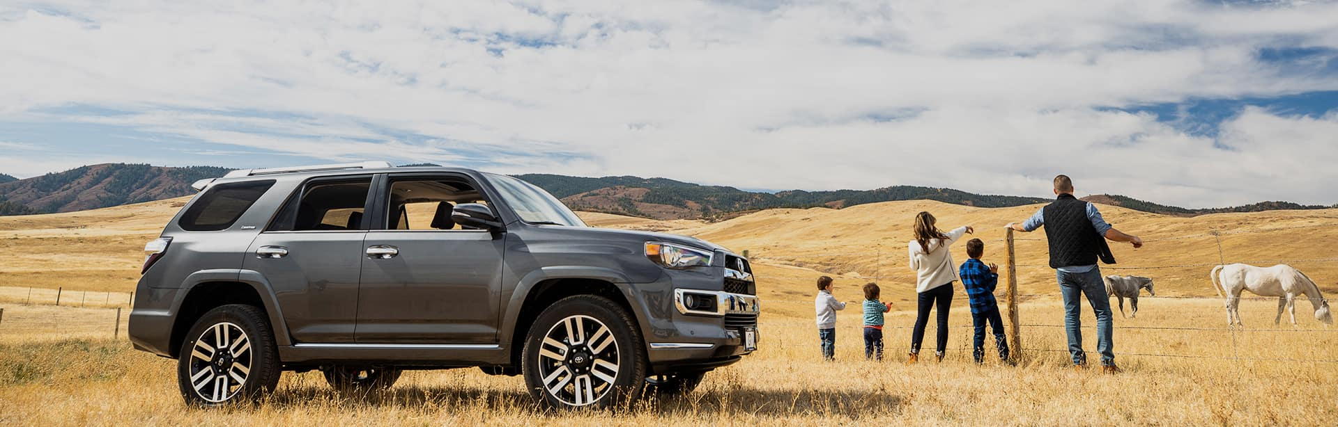 family-watches-horses-next-to-parked-Toyota-SUV
