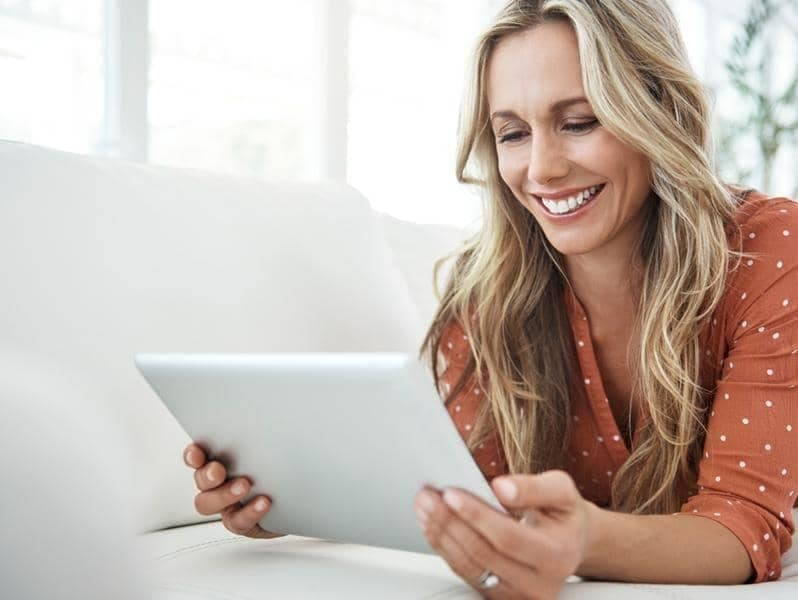 Woman shopping online from a tablet while lying on her sofa.