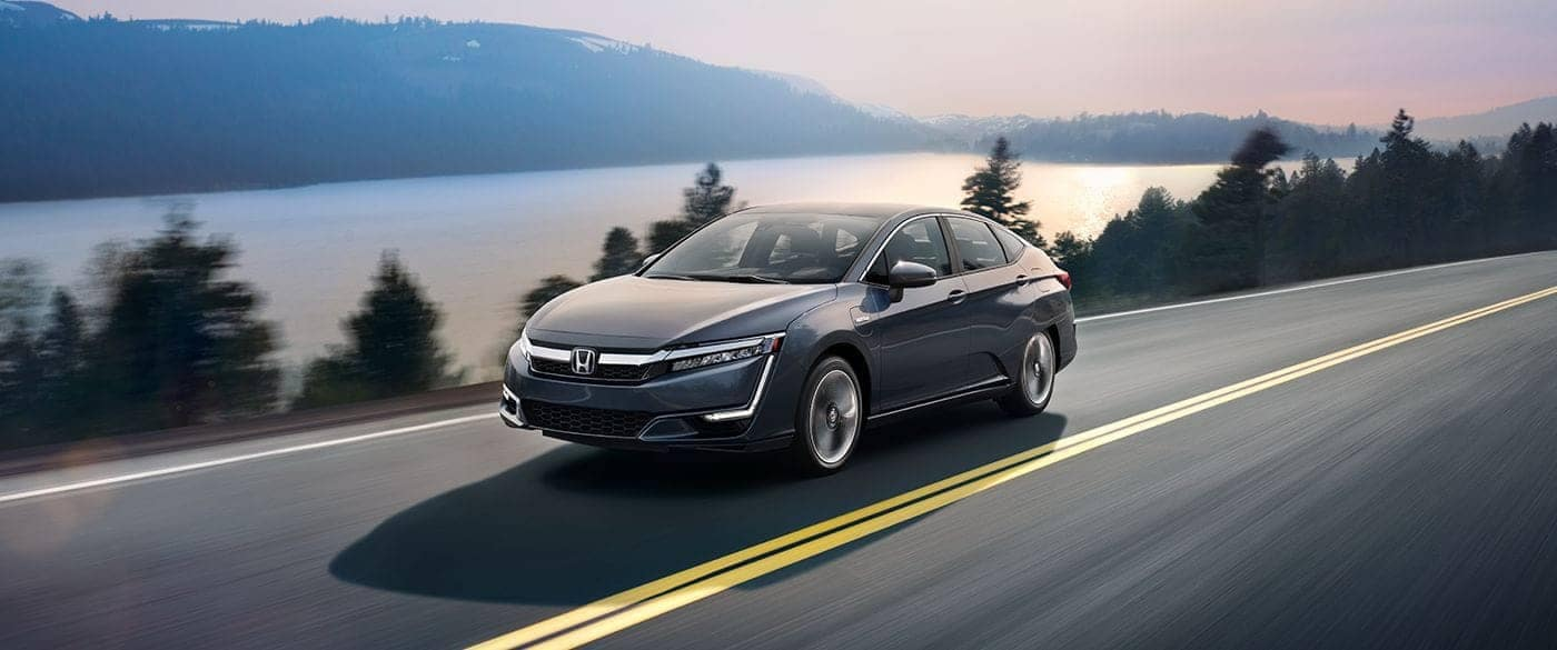 2018 Honda Clarity Plug-In Hybrid driving down a highway next to a lake