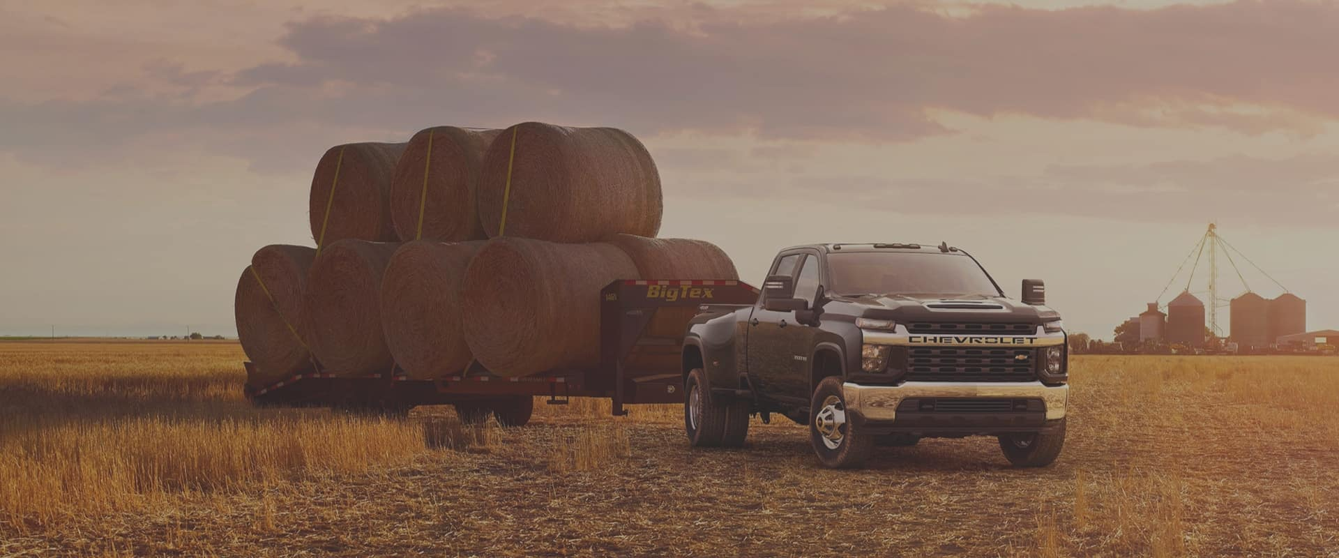 Pickup truck in a field with hay bales behind it