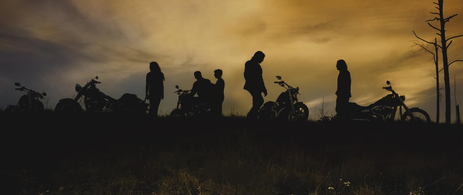 a bunch of people standing around motorcycles at dusk