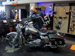 Mechanic switching out the handlebars on a Harley in the fit shop