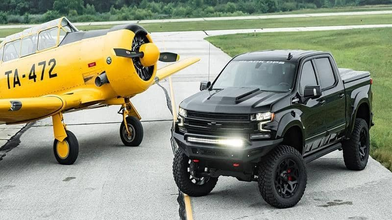 Black Custom Truck Parked next to small yellow plane