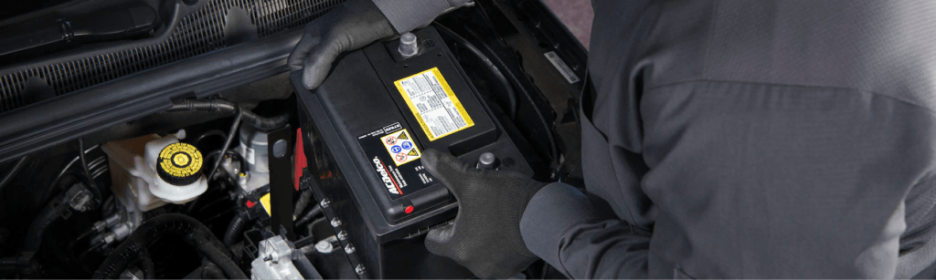 technician installing new AC Delco battery in car engine