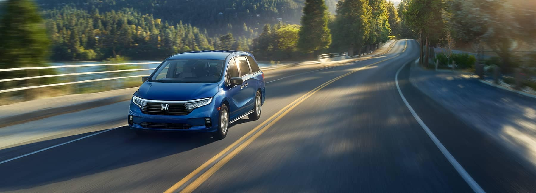 2021 Sapphire Blue Honda Odyssey driving along a mountain road