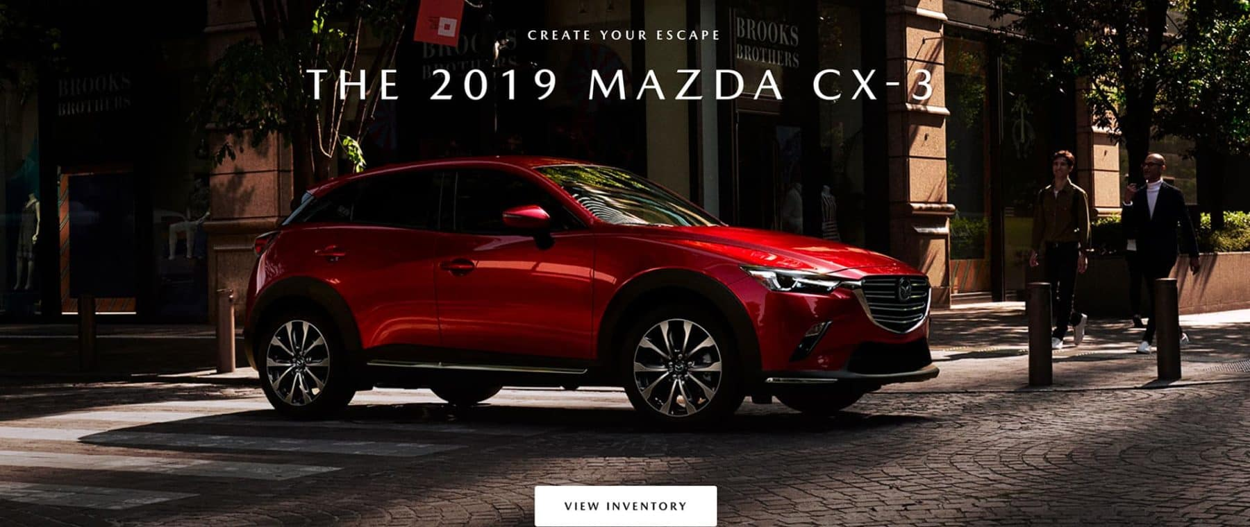 Red 2019 Mazda CX-3 at a brick street city intersection