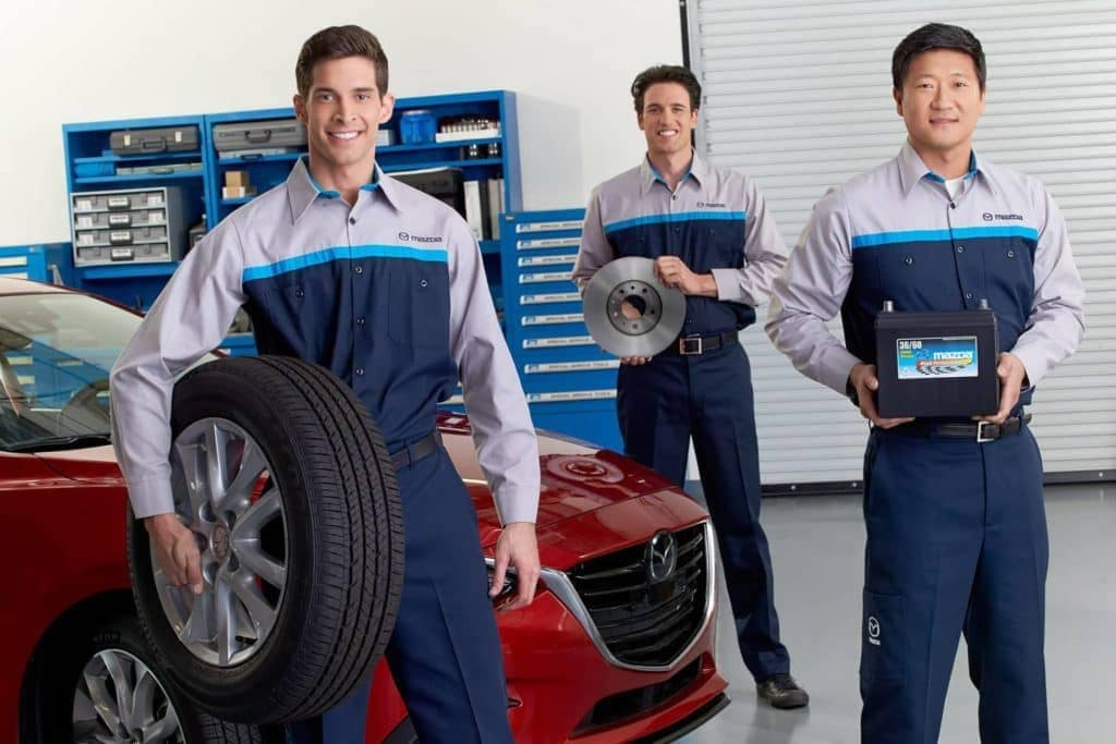 Service technicians holding Mazda parts
